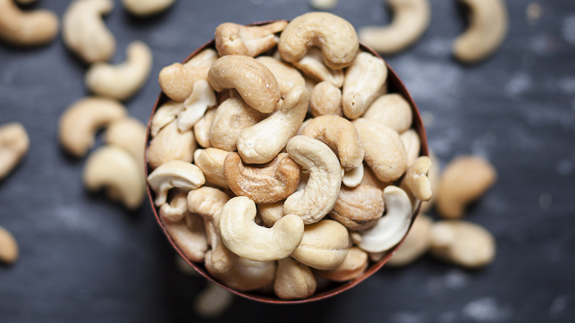 Bowl of roasted and salted cashew nuts on slate